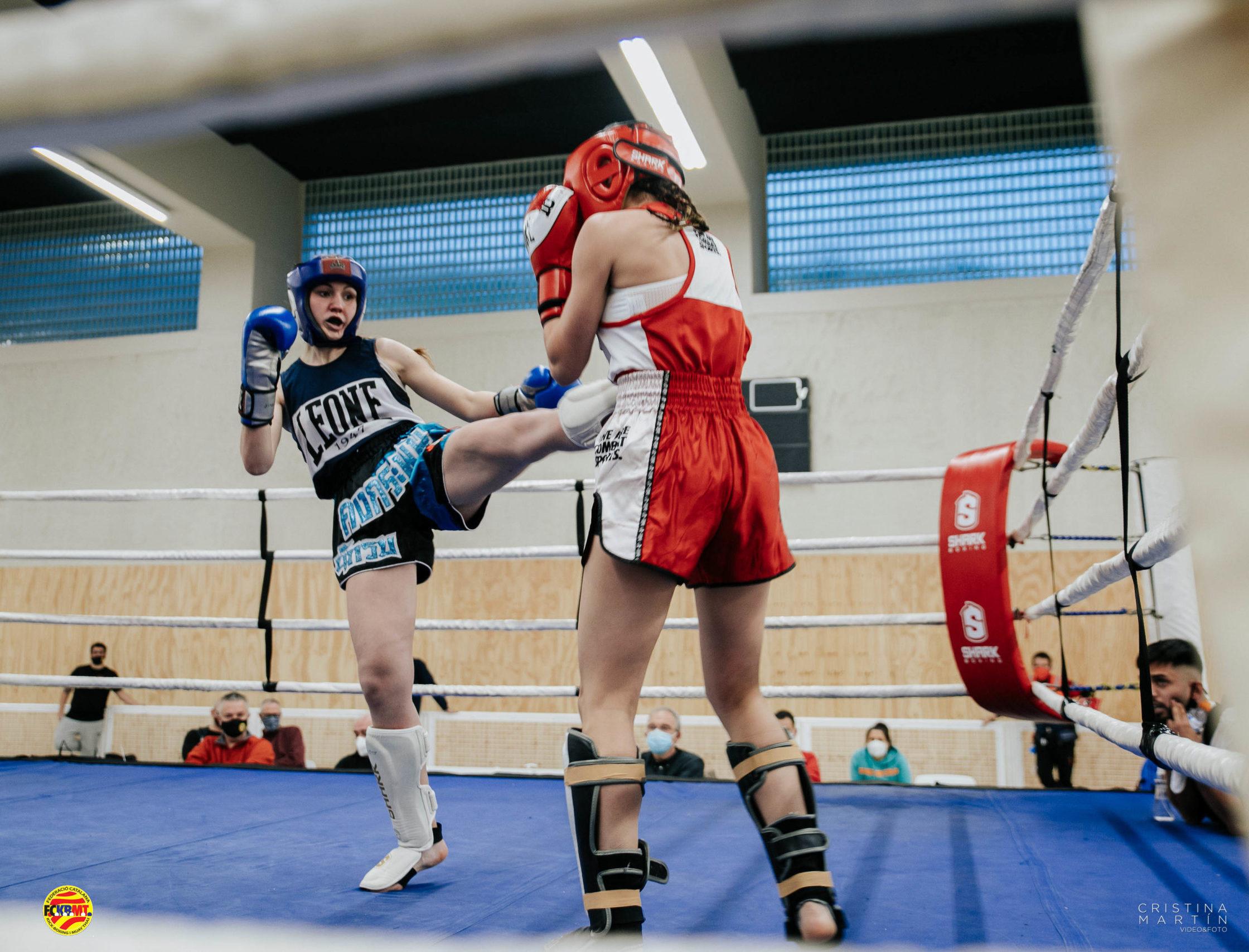 Combate en Ring de chicas con patada frontal de la contrincante de esquina azul